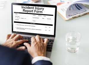 man filling out incident injury report form on laptop